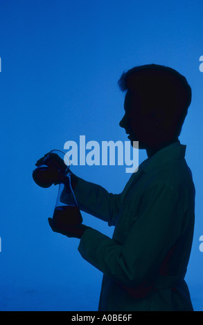Silhouette of female chemist pouring chemicals - Stock Photo