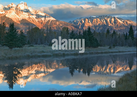 Teton Mountains at sunrise reflected in backwater of Snake River Grand Teton National Park Wyoming - Stock Photo