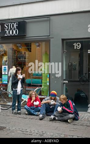 Teenagers eating on pavement, Strøget shopping street, Copenhagen, Denmark, Europe - Stock Photo