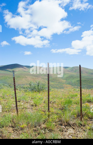 Fence along high desert hills on spring day Umptanum Ridge Eastern Washington USA - Stock Photo