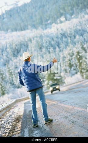 Male hitchhiker wearing cowboy hat on mountain roadside - Stock Photo