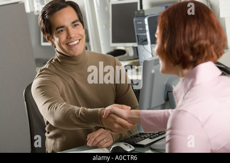 Businessman shaking hands in office - Stock Photo