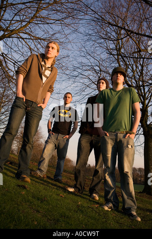 FOUR YOUNG MEN STANDING IN A PARK - Stock Photo