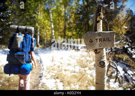 Backpacker hiking though snow lined trail with sign in foreground - Stock Photo