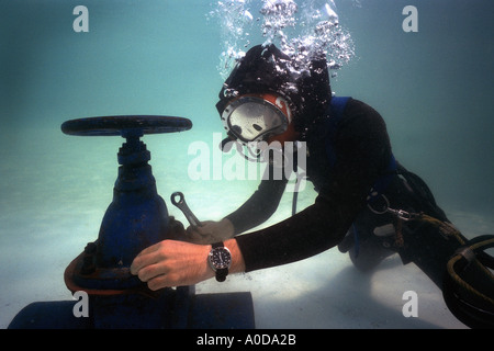 commercial oil rig diver at work underwater on valve in north sea - Stock Photo