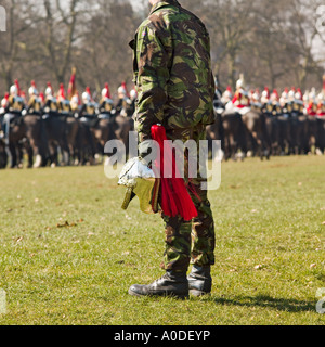 A British soldier holding a discarded helmet from a Household cavalry horseman in Hyde park London England - Stock Photo