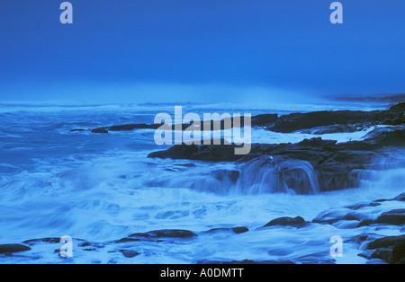 Storm surf hitting rocky coastline at dusk Yachats Wayside State Park Oregon - Stock Photo