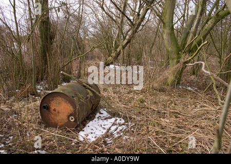 RUSTING OIL CHEMICAL DRUM IN WOODLANDS DURING WINTER WITH SNOW ON THE GROUND - Stock Photo