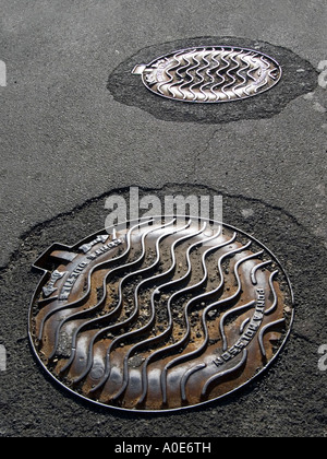 two cast-iron manhole covers in a street in St Amant de Boix Poitou France - Stock Photo