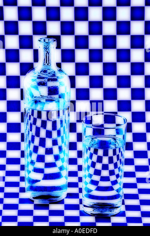 bottle and glass against checkerboard background - Stock Photo