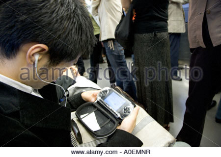 young Japanese man watching a movie on his sony play station while commuting to work - Stock Photo