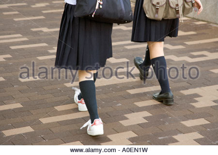 two Japanese students in uniform walking in unison - Stock Photo