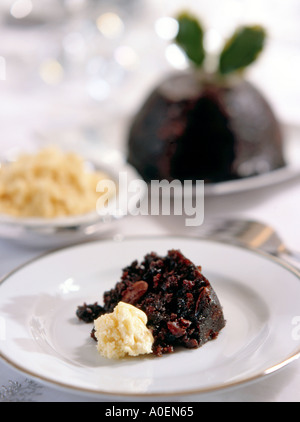 Portion of traditional English Christmas pudding served with brandy butter - Stock Photo