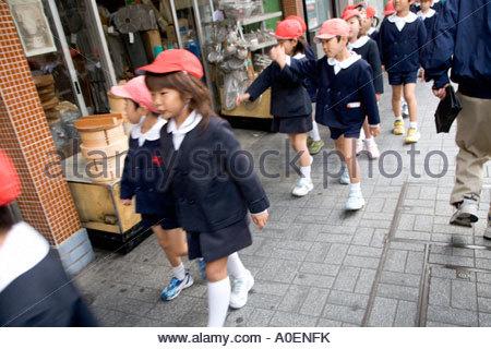 school children walking in a group japan - Stock Photo