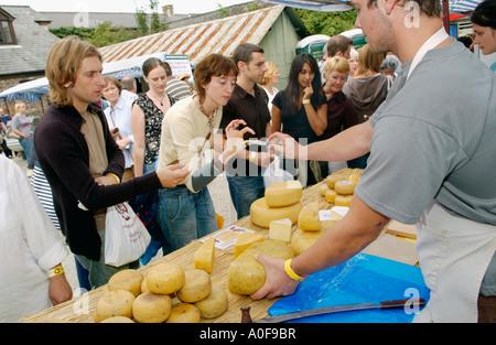 People tasting Teifi Farmhouse Cheese of Llandysul Ceredigion at the annual Abergavenny Food Festival Wales UK GB - Stock Photo