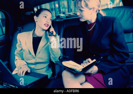 Two businesswomen sitting in a car - Stock Photo