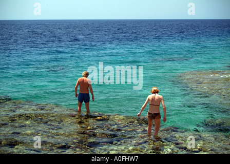 A youngmale and female tourist walking carefully on underwater rocks in the Red Sea at Naama Bay Sharm El Sheikh - Stock Photo