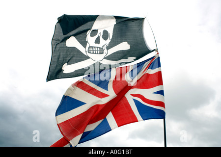 Jolly Roger pirate flag flies above the British Union Flag - Stock Photo