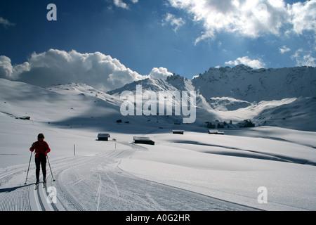 Cross country skier on the Alpe di Siusi Seiseralm plateau in the Italian Dolomites, backed by the Denti di Terrarossa - Stock Photo