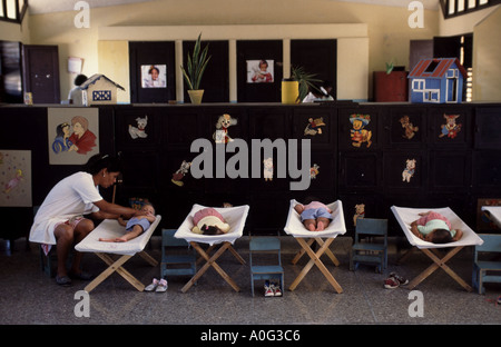 A Cuban woman tends to small child napping in creche or day care center in Havana Cuba - Stock Photo