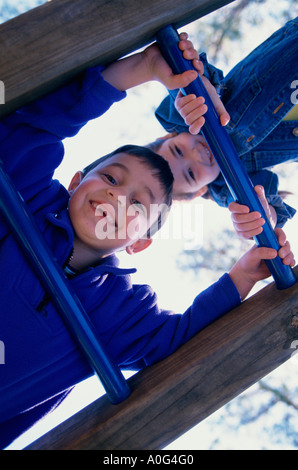 Portrait of a boy and a girl climbing on monkey bars - Stock Photo