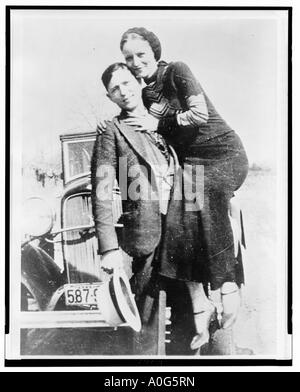 Clyde Barrow holding Bonnie Parker on one arm facing front in front of automobile - Stock Photo