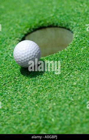 Golf ball on edge of hole on golf green - Stock Photo