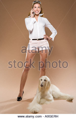 Woman with cell phone and dog - Stock Photo