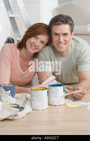 Smiling couple picking out paint colors - Stock Photo