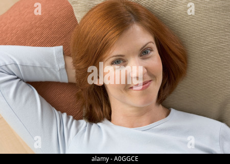 Smiling redheaded woman lying on pillows - Stock Photo