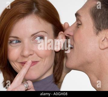 Man whispering secret in woman s ear - Stock Photo