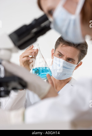 Scientists with microscope and blue liquid - Stock Photo