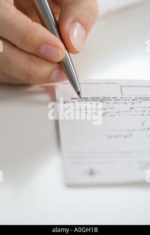 Closeup of hand writing prescription - Stock Photo