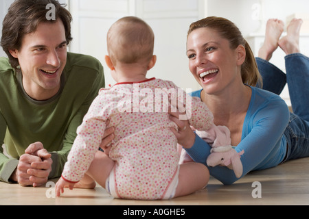 Couple playing with baby on floor - Stock Photo