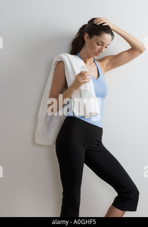 Woman in workout clothes looking down - Stock Photo