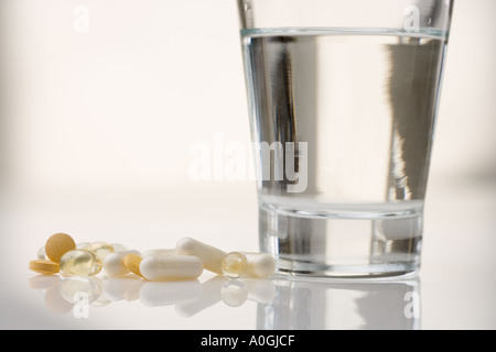 Pile of pills with water glass - Stock Photo