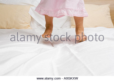 Girl jumping on a bed - Stock Photo