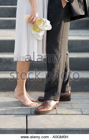 Smartly dressed couple on steps - Stock Photo