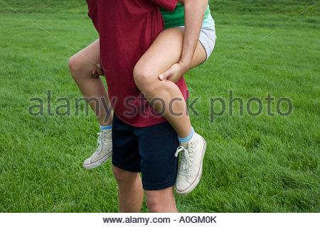 Man giving woman a piggyback - Stock Photo