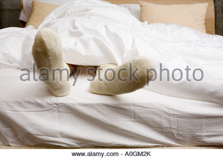 Person wearing socks in bed - Stock Photo