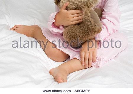 Girl hugging a teddy bear - Stock Photo