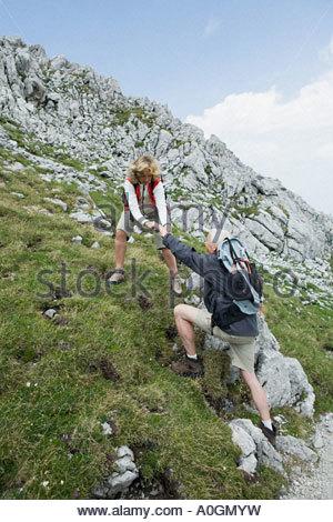 Wife helping husband up slope - Stock Photo