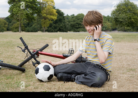 Teenage boy on cellphone in park - Stock Photo