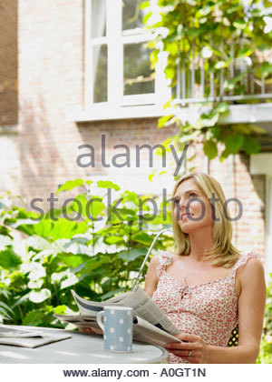 Woman in garden with newspaper - Stock Photo
