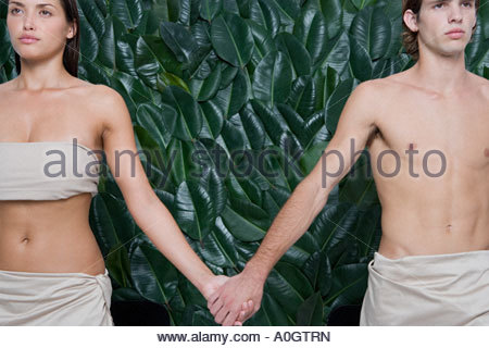 Young woman and man holding hands - Stock Photo