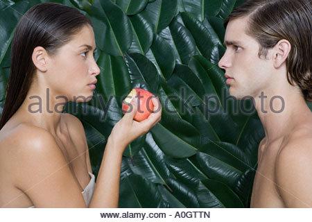 Woman holding half eaten apple opposite man - Stock Photo