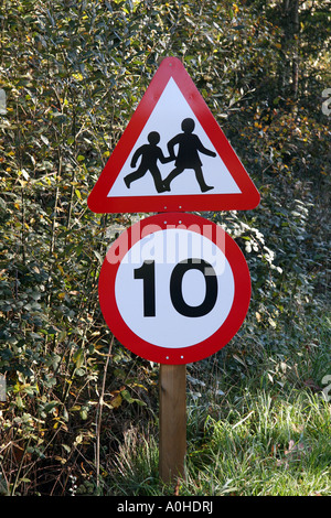 road sign warning of children crossing 10 mile an hour speed limit - Stock Photo