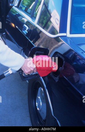 USA New York City NYC Woman Filling a Car With Gasoline Putting Petrol in an Automobile - Stock Photo