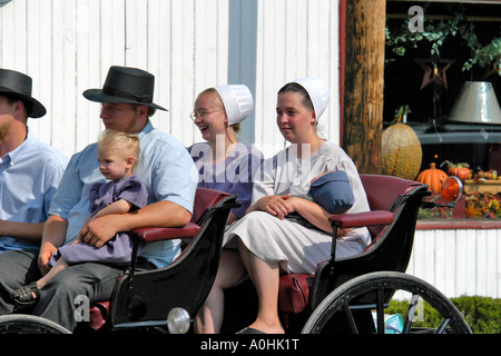 Amish family riding in an open horse drawn buggy in Shipshewana, Indiana - Stock Photo