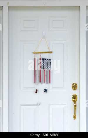 American flag wind chimes hanging on a white entry door - Stock Photo